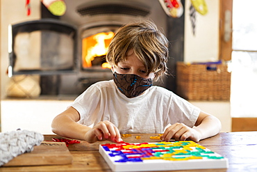 young boy wearing mask playing board game at home