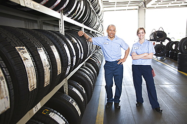 Portrait of smiling male and female mechanic by a rack of tyres in a workshop