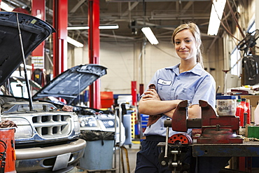 Portrait of young female Caucasian mechanic in auto repair shop