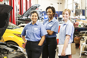 Portrait of three smiling female mechanics in auto repair shop