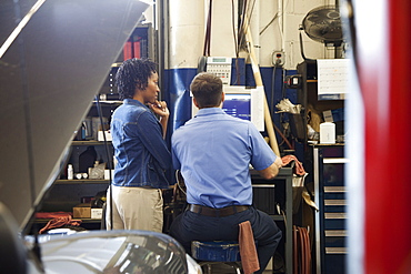 Mechanic and customer look at computer screen in auto repair shop