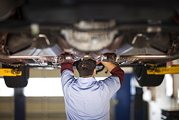 Mechanic in a repair shop works on the underside of a car up on a lift