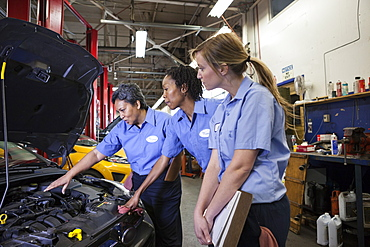 Three female mechanics look inside the engine compartment of a car in a repair shop