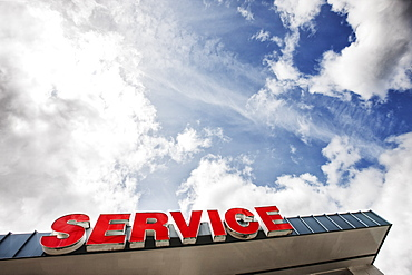 Auto service sign against partly cloudy blue sky viewed from below