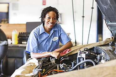 Portrait of smiling black female mechanic in auto repair shop