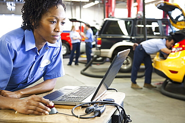 Female mechanic using a laptop, diagnostic electronics, in an auto repair shop