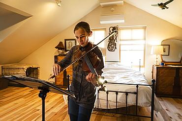Teenage girl playing her violin in her bedroom