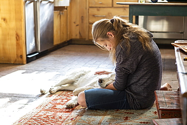 Teenage girl stroking her English Cream Golden Retriever dog