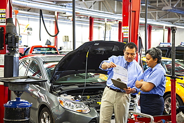 Owner of auto repair shop talks with Hispanic female mechanic