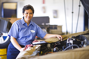 Portrait of female hispanic mechanic in auto repair shop