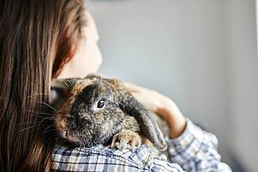 Portrait of pet house rabbit on shoulder of woman, Bristol, United Kingdom