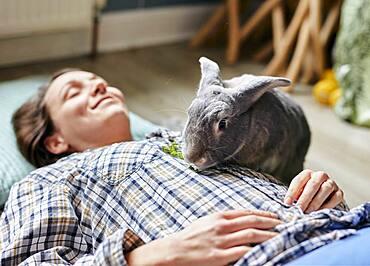 Pet house rabbit eating food on top of woman lying on floor, Bristol, United Kingdom