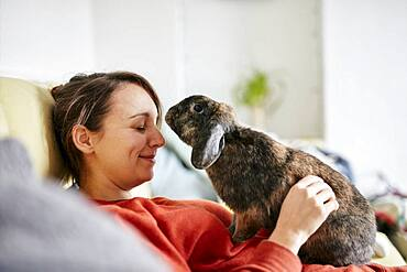 Pet house rabbit reaching towards woman with eyes closed on sofa, Bristol, United Kingdom