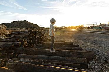 7 year old boy standing alone on railroad ties at sunset, New Mexico, United States of America