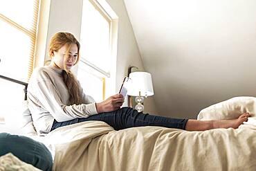 teenage girl lying in bed using her smart phone