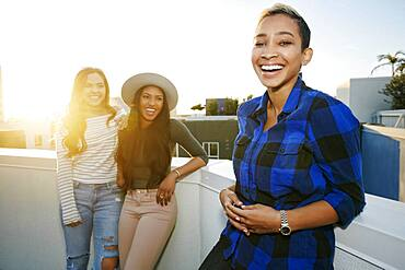 Three young women on a rooftop at dusk