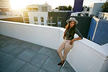 Young woman leaning on a parapet at sunset, city buildings in the background.