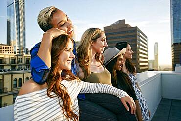 A group of young women partying on a city rooftop at dusk