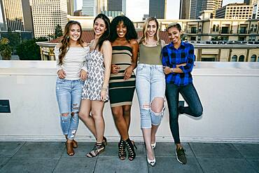 Five young women posing for photographs on a rooftop, city skyline background