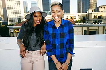 Two young women on a rooftop posing for photographs, city skyline background.