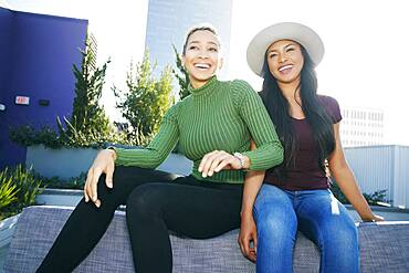 Two young women on a rooftop posing for photographs