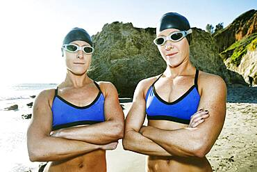 Two sisters, triathletes in training in swimwear, swimhats and goggles.
