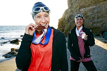 Two sisters, triathletes in training wearing their large medals, winners.