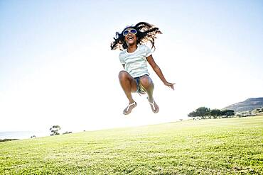 Young mixed race girl with long curly hair leaping in the air