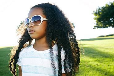Young mixed race girl wearing sunglasses