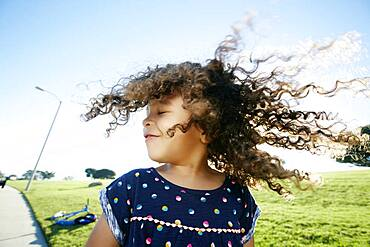 Young mixed race girl aged 4 outdoors, curly hair fanning out