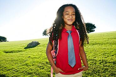 Young mixed race girl in pink shirt and formal tie, wearing a backpack
