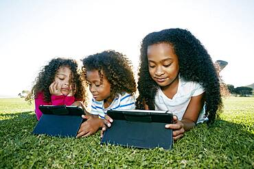 Young mixed race girl and her brother and sister with two digital tablets, screen time