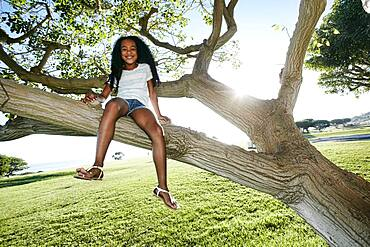 Young mixed race girl sitting in a tree branch