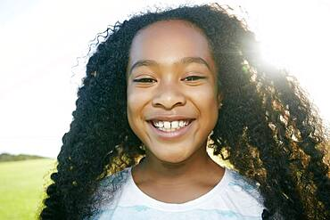 Young mixed race girl with long curly black hair, smiling