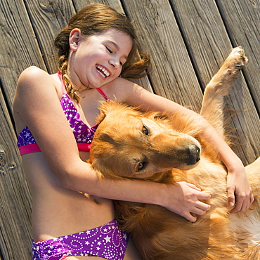 A girl in a bikini lying beside a golden retriever dog, viewed from above, Austin, Texas, USA