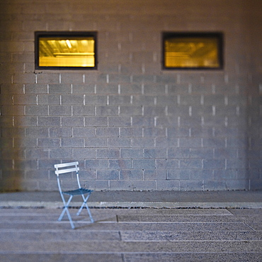 Folding chair in front of concrete block wall
