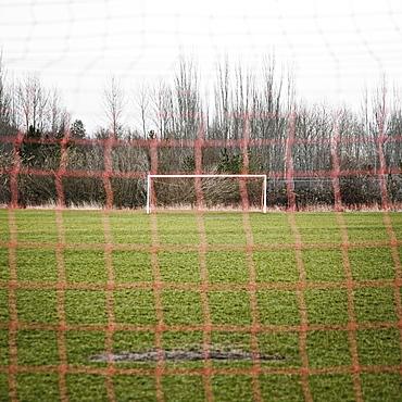 Soccer field seen through soccer goal net
