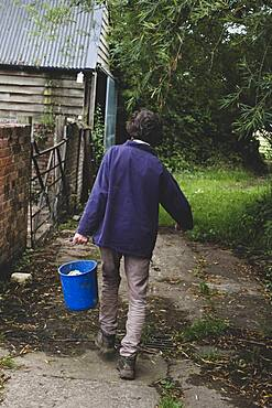 Rear view of woman on a farm, carrying blue plastic bucket.