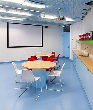 Classroom with white board, round tables and counter and sink