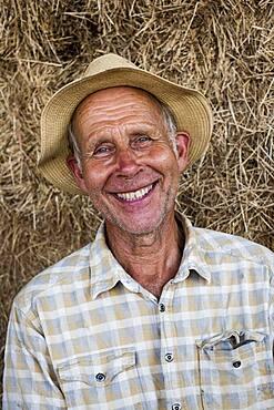 Smiling man wearing sun hat, looking at camera.