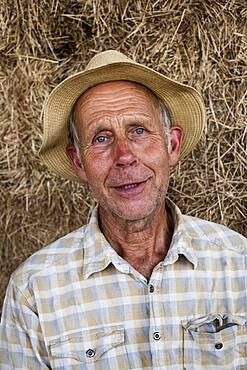 Farmer wearing checked shirt and sun hat, looking at camera.