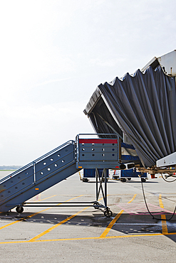 A set of steps and a mobile airport departure passenger tunnel, air bridge