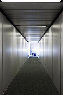 An empty narrow tunnel or corridor, a passenger airbridge.