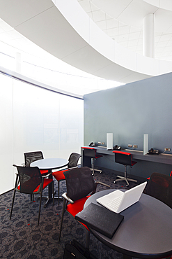 A business centre, tables and chairs, laptops and telephones.