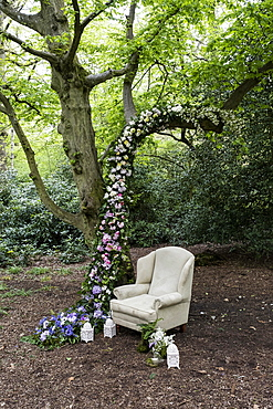 Armchair and flower garland decorations for a woodland naming ceremony.