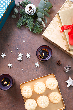 Christmas, overhead view of mince pies on a plate and star shapes and lit candles.