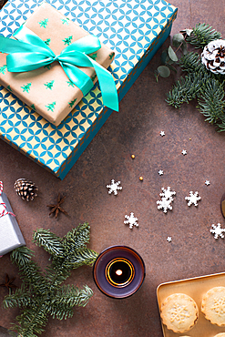 Christmas, overhead view of gifts, mince pies on a plate and lit candles.