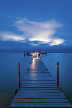 Jetty dock onto ocean at dawn with dramatic sky above.