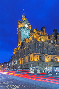 Clock tower of Balmoral Hotel lit up at night with traffic light blur below.