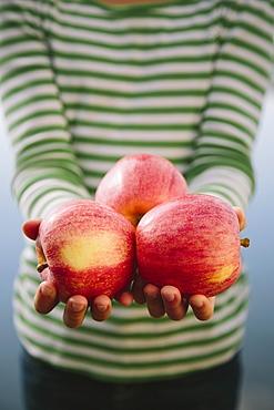 Nine year old girl holding handful of organic apples, Seattle, Washington, USA
